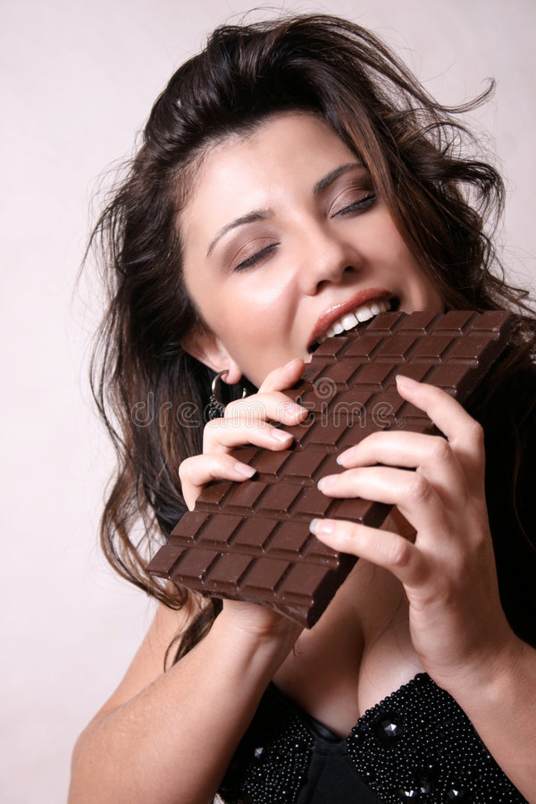 Chocoholic. Woman with a large bar of chocolate royalty free stock image