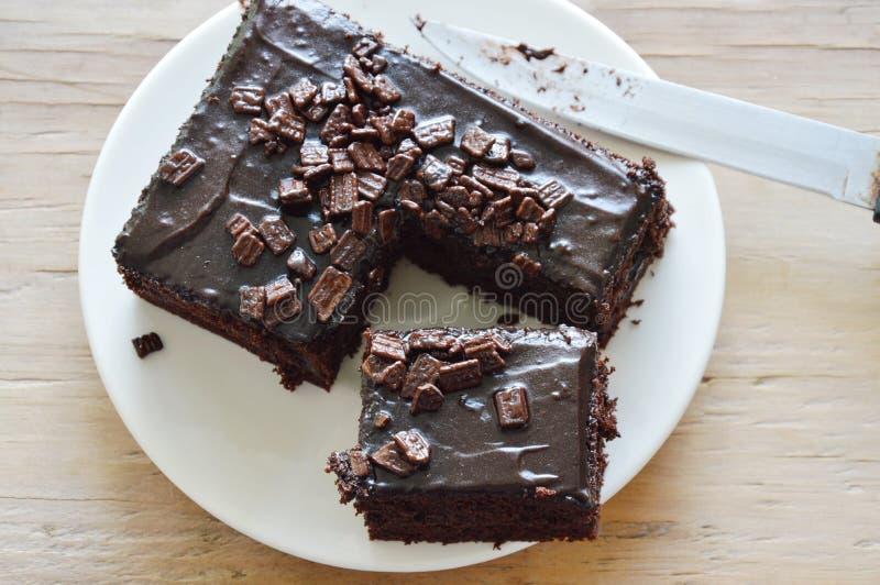 Chocolade boterdiecake voor stuk en messenblad wordt gesneden op schotel stock afbeelding