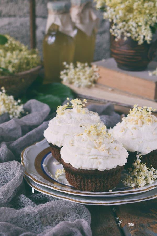 Chocolade capcakes met vanilleroom met witte chocolade en vlierbesbloemen wordt bestrooid die Uitstekende stijl De ruimte van het stock afbeelding