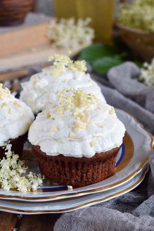 Chocolade capcakes met vanilleroom met witte chocolade en vlierbesbloemen wordt bestrooid die Uitstekende stijl De ruimte van het stock foto