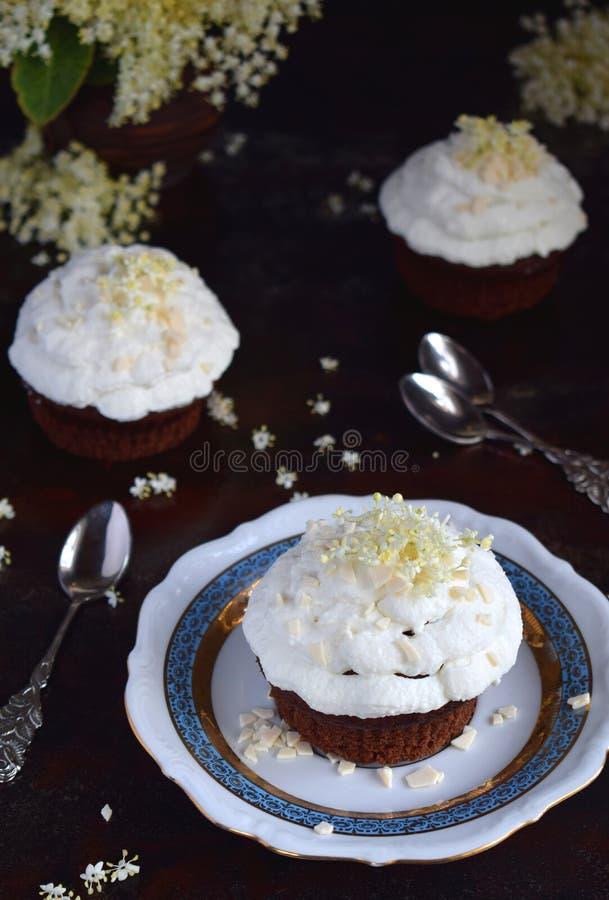 Chocolade capcakes met vanilleroom met witte chocolade en vlierbesbloemen wordt bestrooid die Uitstekende stijl De ruimte van het royalty-vrije stock afbeelding