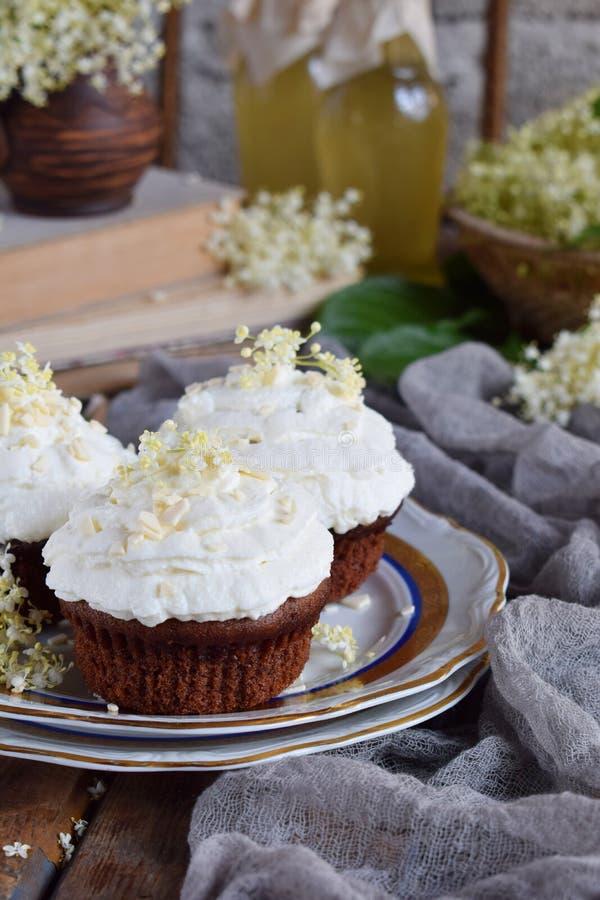 Chocolade capcakes met vanilleroom met witte chocolade en vlierbesbloemen wordt bestrooid die Uitstekende stijl De ruimte van het royalty-vrije stock foto's
