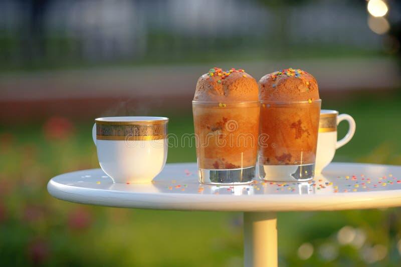 Chocolade cupcakes en verse thee in tuin stock afbeelding