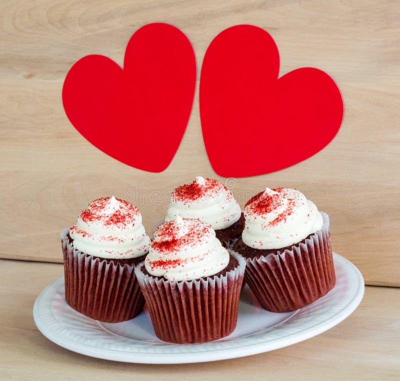 chocolade 4 cupcakes met het wit berijpen en rood bestrooit onder 2 rode harten royalty-vrije stock foto