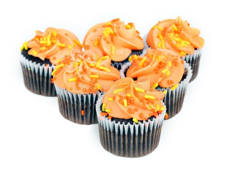 Chocolade cupcakes met oranje suikerglazuur op wit stock foto's