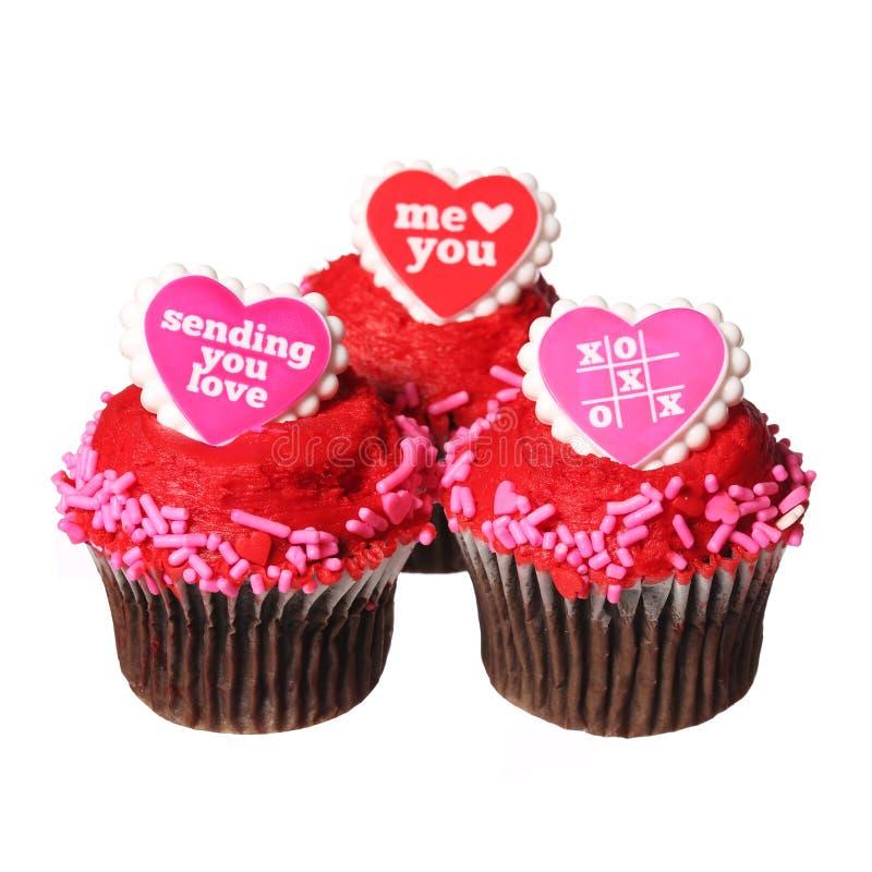 Chocolade cupcakes met rode harten op de geïsoleerde bovenkanten, stock foto