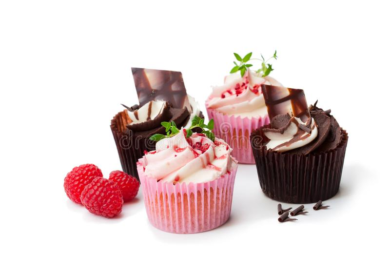 Chocolade cupcakes met verse geïsoleerde frambozen en room royalty-vrije stock fotografie