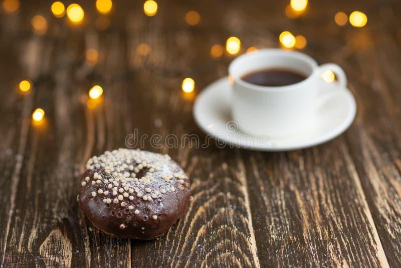 Chocolade donuts met koffie op een houten lijst met mooie lichten stock foto