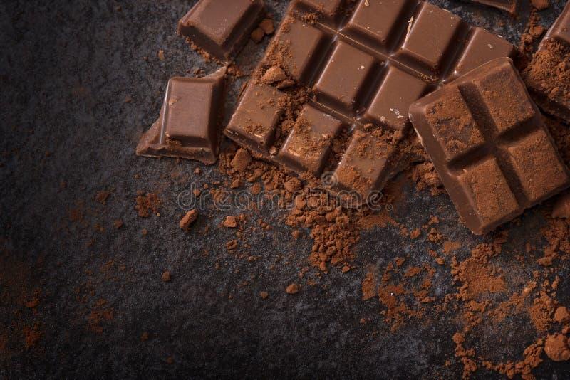 Chocolade en cacaopoeder op een donkere leiachtergrond met exemplaar stock foto