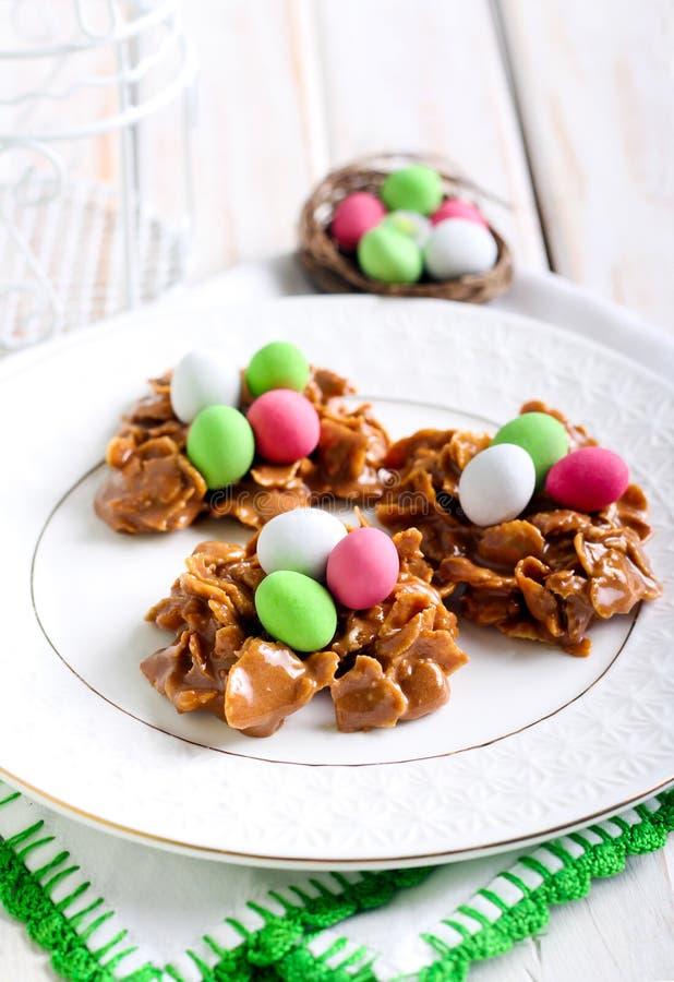 Chocolade en cornflakesnesten met suikergoedeieren stock foto