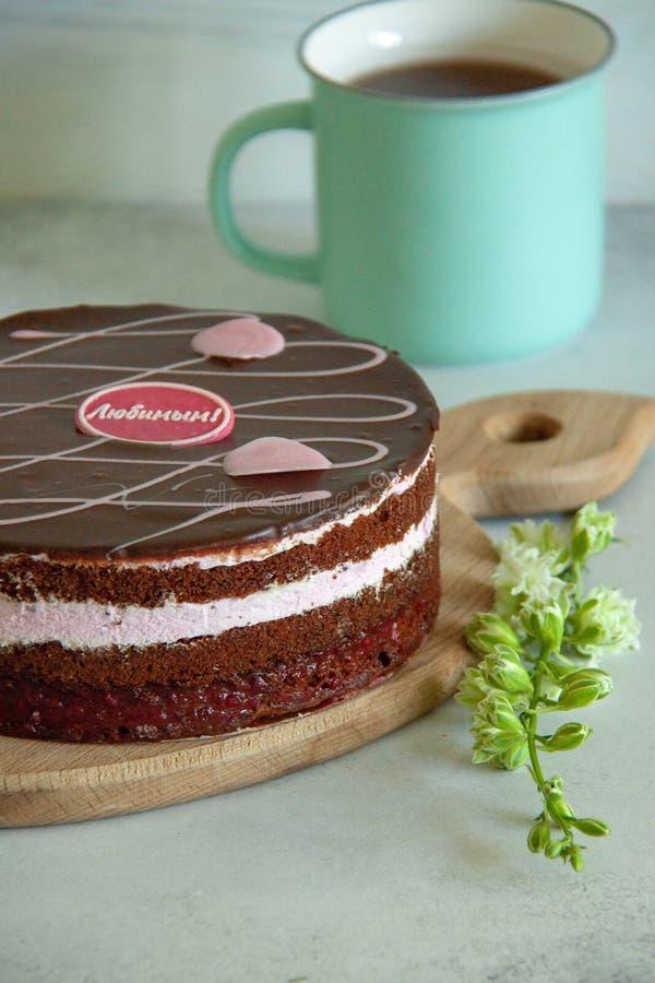Chocolade en frambozencake op een bruine raad met witte bloemen stock foto