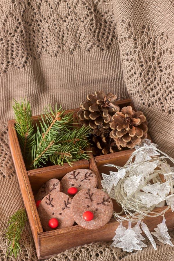 Chocolade feestelijke koekjes in de vorm van een hert Rudolph met een rode die neus door feestelijk decor wordt omringd stock fotografie