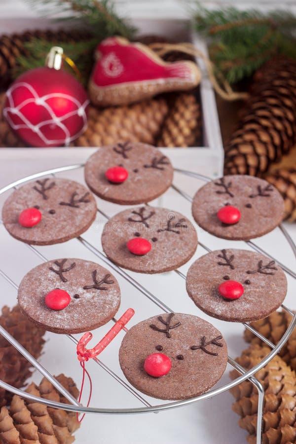 Chocolade feestelijke koekjes in de vorm van een hert Rudolph met een rode die neus door feestelijk decor wordt omringd royalty-vrije stock afbeelding