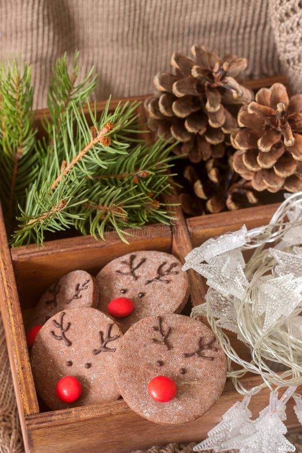 Chocolade feestelijke koekjes in de vorm van een hert Rudolph met een rode die neus door feestelijk decor wordt omringd royalty-vrije stock foto
