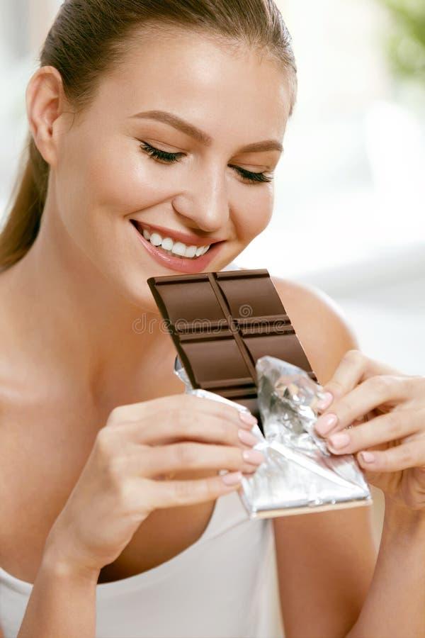 Chocolade Gelukkige Vrouw het Bijten Chocoladereep stock fotografie