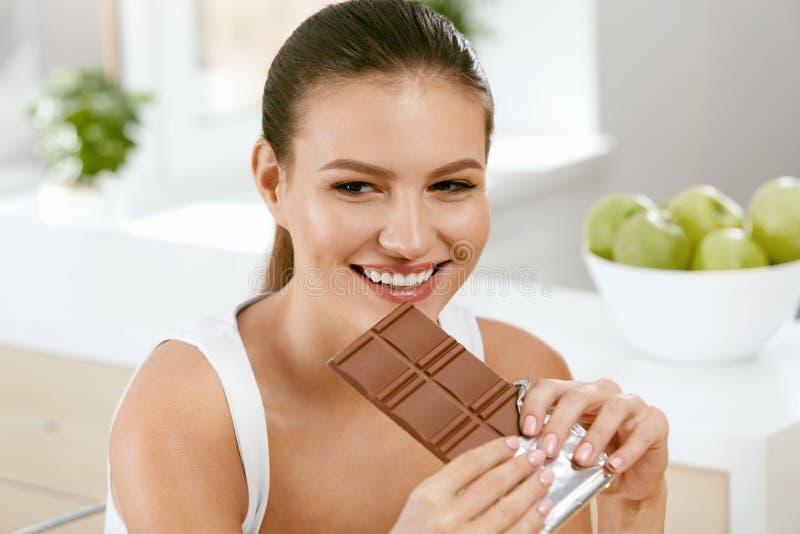 Chocolade Gelukkige Vrouw het Bijten Chocoladereep stock afbeeldingen