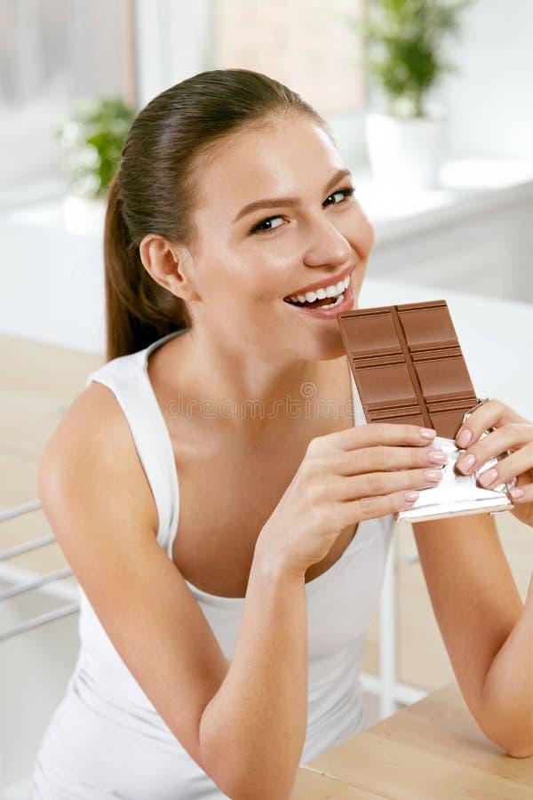 Chocolade Gelukkige Vrouw het Bijten Chocoladereep stock foto's
