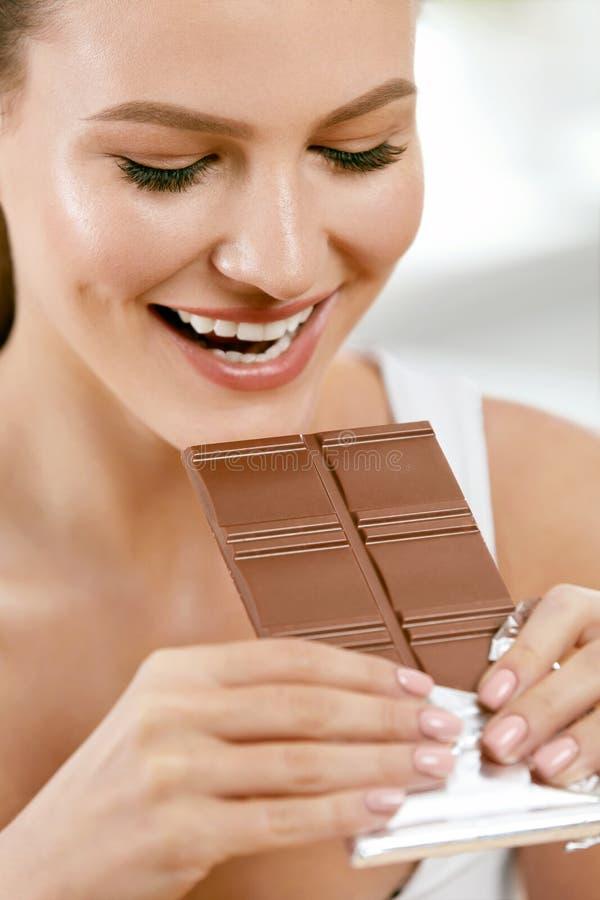 Chocolade Gelukkige Vrouw het Bijten Chocoladereep royalty-vrije stock foto