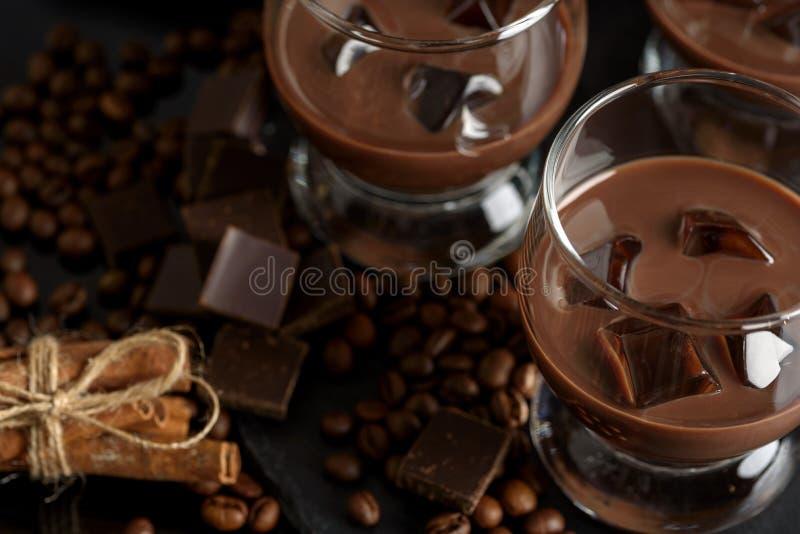 Chocolade, koffie, romige likeur, cocktail met koffiebonen, chocolade en kaneel Op een zwarte achtergrond Alcoholische Kerstmis royalty-vrije stock foto's