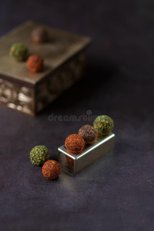 Chocolade om suikergoed dat met kruiden op een donkere achtergrond wordt bestrooid stock foto