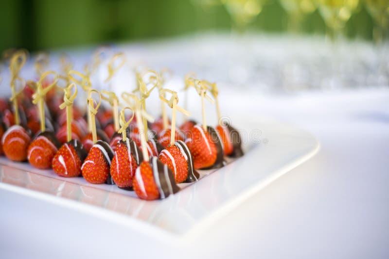 Chocolade ondergedompelde aardbeien op een plaat bij een huwelijkslijst stock fotografie