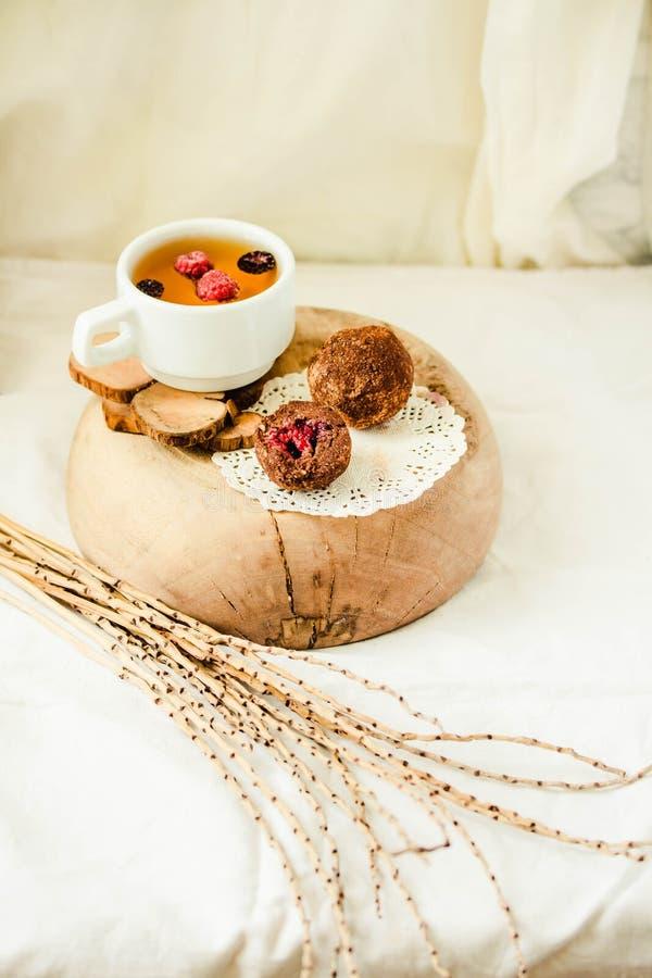 Chocoladeballen met verse bessen in de houten plaat op wit linnentafelkleed backgound Een kop van aftreksel Kinfolk en royalty-vrije stock foto