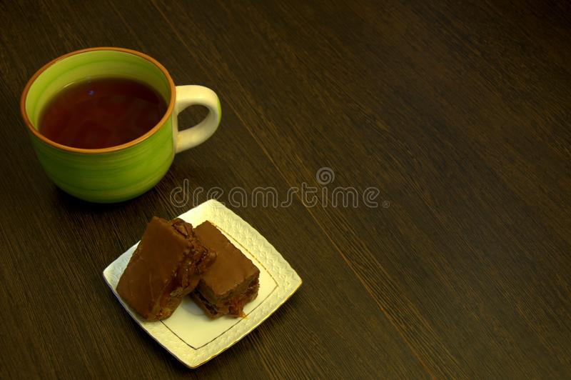 Chocoladebiscuitgebak op een witte porseleinplaat en een kop thee royalty-vrije stock afbeeldingen