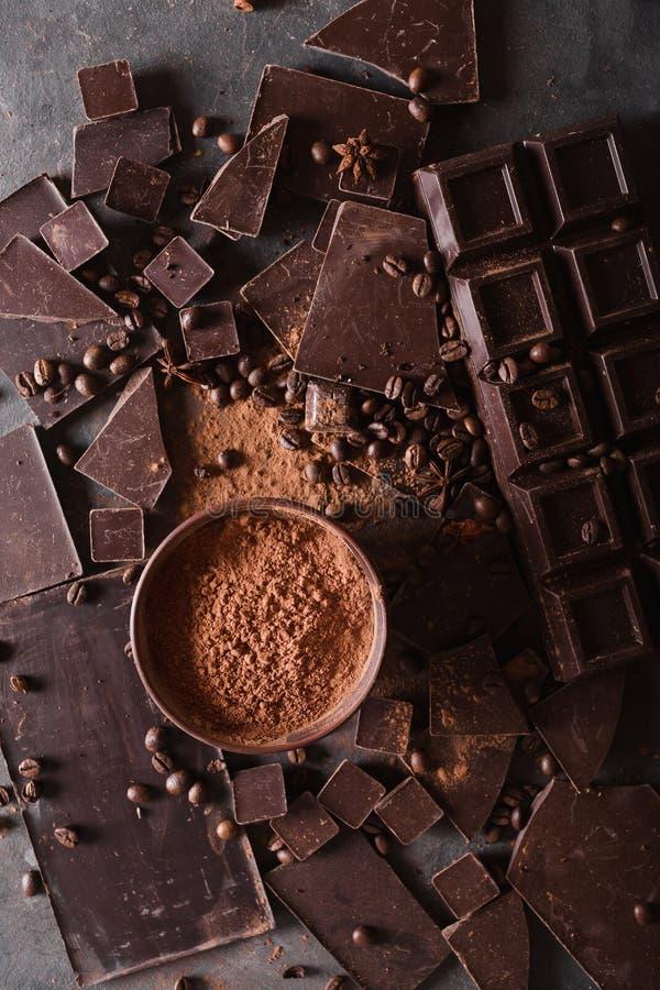 Chocoladebrokken en cacaopoeder De Chocoladereepstukken van koffiebonen Grote reep chocolade op grijze abstracte achtergrond stock foto's