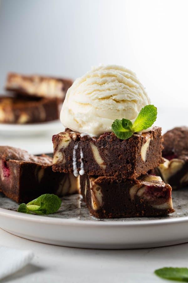 Chocoladebrownie met vanilleroomijs, rasberry en munt op een witte achtergrond De ruimte van het exemplaar stock fotografie