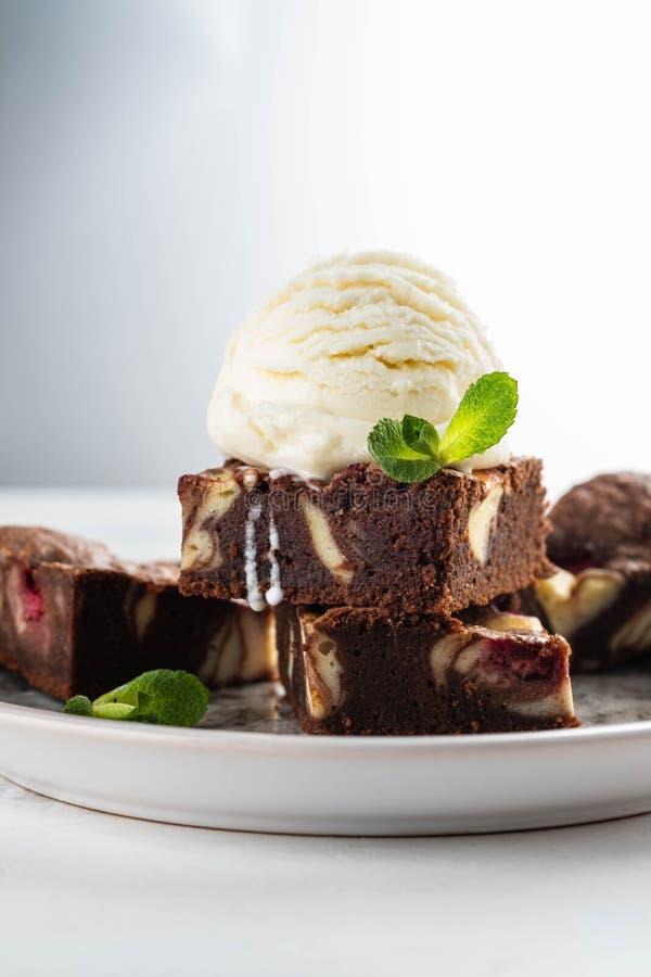 Chocoladebrownie met vanilleroomijs, rasberry en munt op een witte achtergrond De ruimte van het exemplaar stock afbeelding