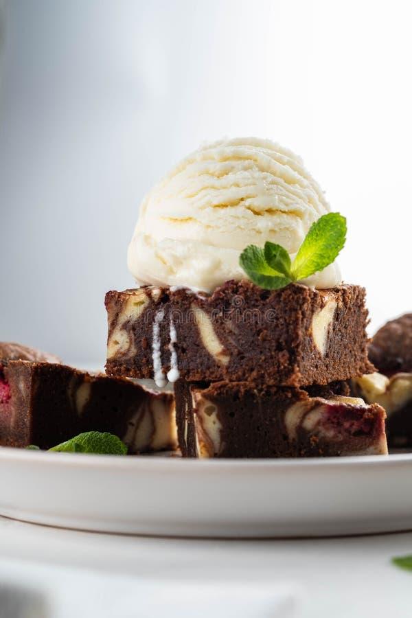 Chocoladebrownie met vanilleroomijs, rasberry en munt op een witte achtergrond De ruimte van het exemplaar stock foto