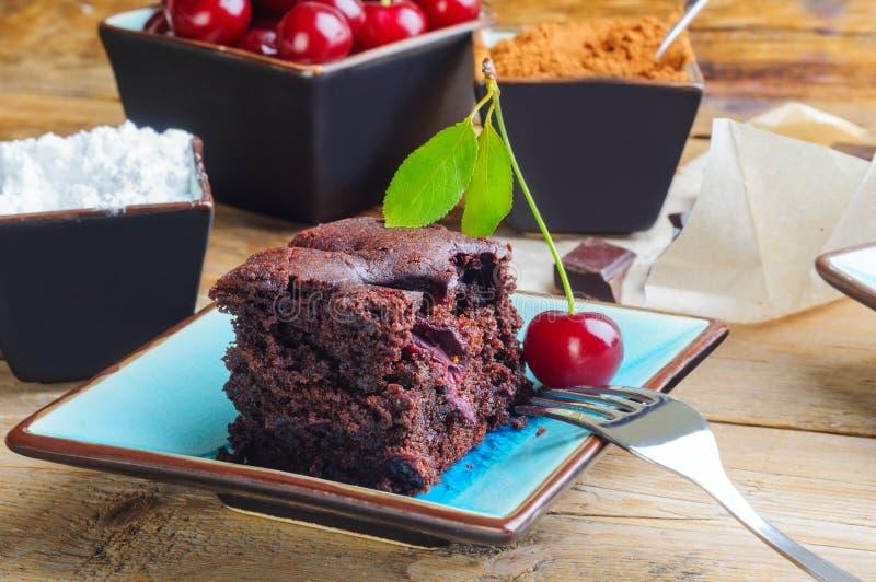 Chocoladecake - brownie - met kersen wordt verfraaid die stock foto