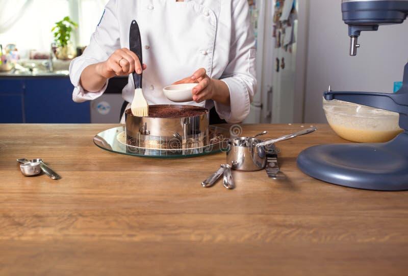 Chocoladecake die op keukenlijst voorbereidingen treffen met keukengerei stock fotografie
