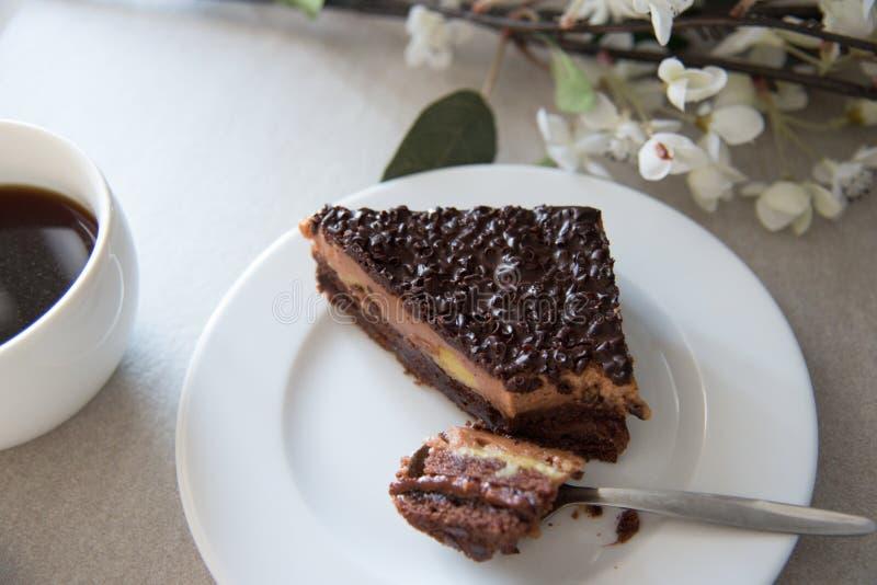 Chocoladecake en koffie met witte bloemen op de achtergrond stock afbeeldingen