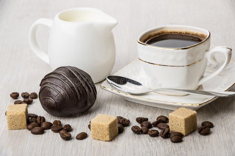 Chocoladecake, kruikmelk, stukken van suiker en koffiekop stock afbeelding