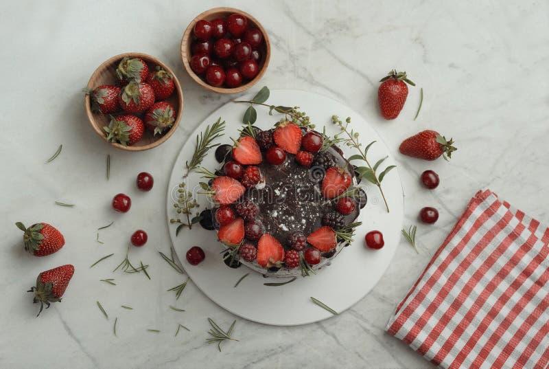 Chocoladecake met aardbeien en braambes en morellen wordt verfraaid die stock afbeeldingen