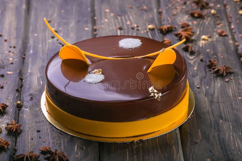 Chocoladecake met decor en koekje, gelei, bessen en munt op een houten tribune stock afbeelding