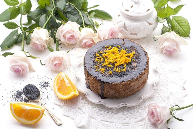 Chocoladecake met sinaasappel en suikerglazuur Op een witte achtergrond, en een boeket van witte rozen Goedemorgen met een verras stock foto's