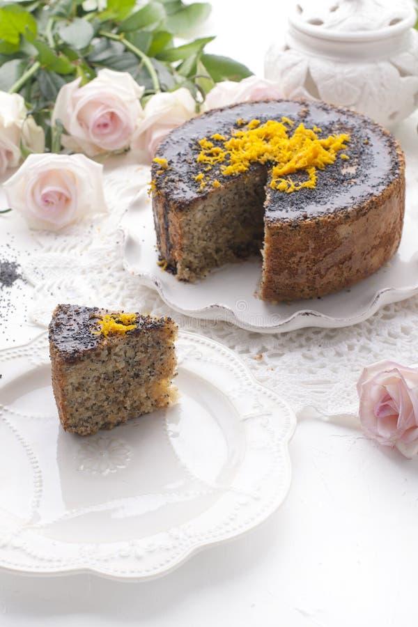 Chocoladecake met sinaasappel en suikerglazuur Op een witte achtergrond, en een boeket van witte rozen Goedemorgen met een verras stock foto