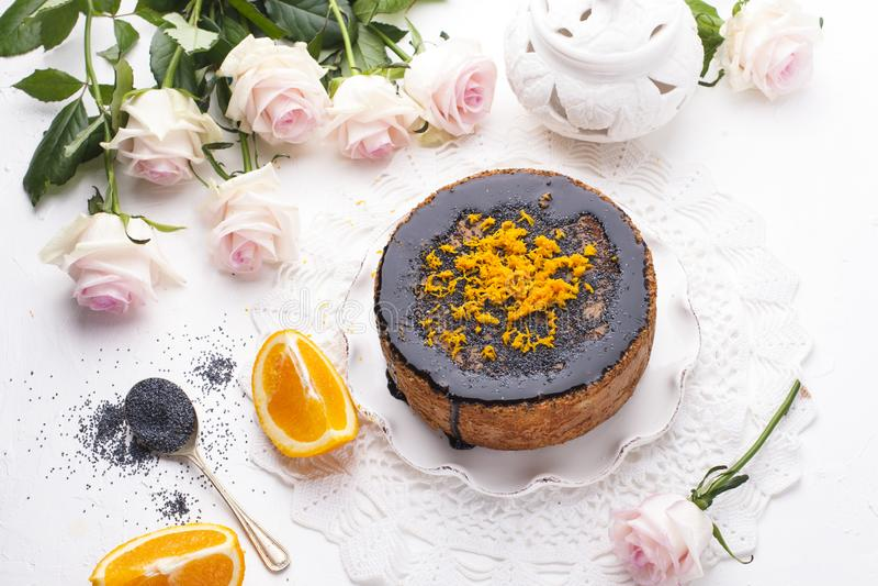 Chocoladecake met sinaasappel en suikerglazuur Op een witte achtergrond, en een boeket van witte rozen Goedemorgen met een verras royalty-vrije stock fotografie
