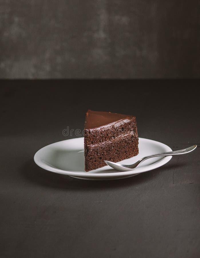 Chocoladecake op donkere humeurige achtergrond Gevoelige bakkerij, stock fotografie