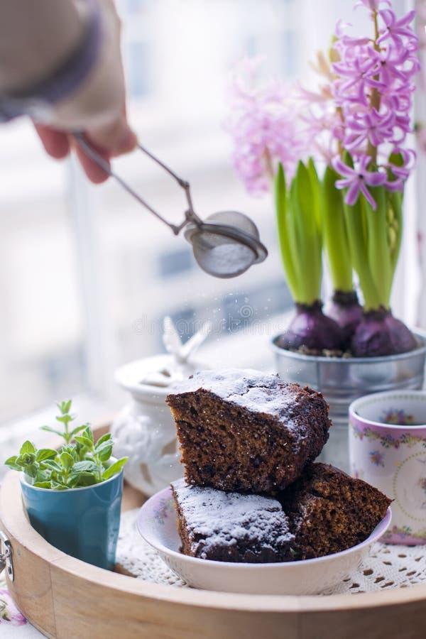 Chocoladecake voor ontbijt, en bloemen, dichtbij het venster Vrouwelijke hand op de foto Vrije ruimte voor tekst De ruimte van he stock afbeeldingen