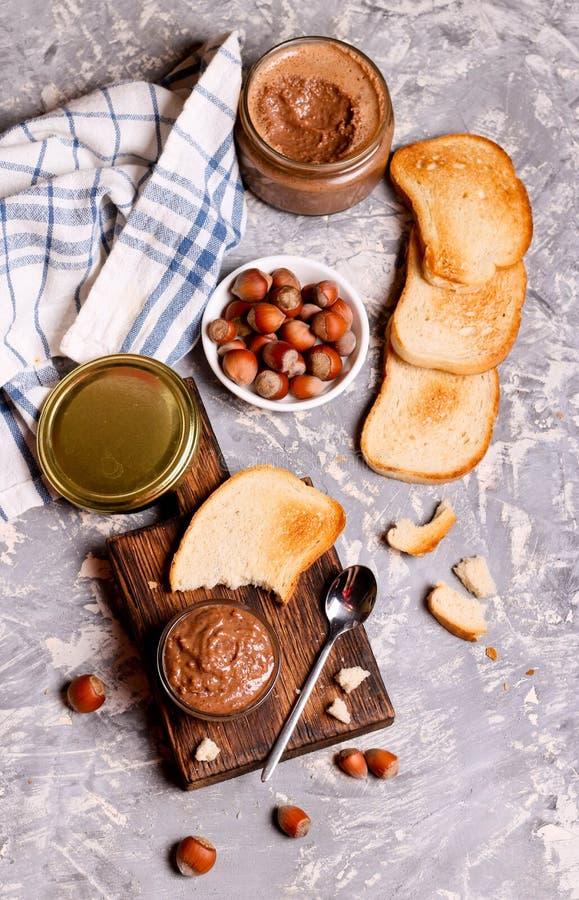 Chocoladedeeg met hazelnoten en brood voor ontbijt wordt uitgespreid dat stock foto