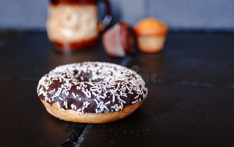 Chocoladedoughnut met muffins op achtergrond stock fotografie