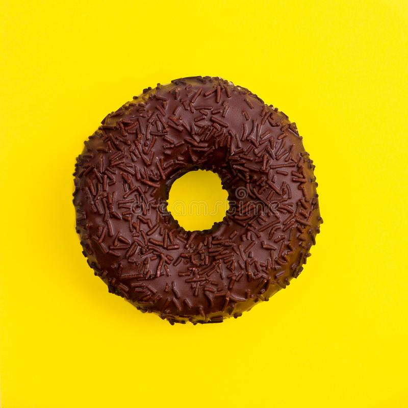 Chocoladedoughnut op een gele hoogste mening als achtergrond royalty-vrije stock foto's