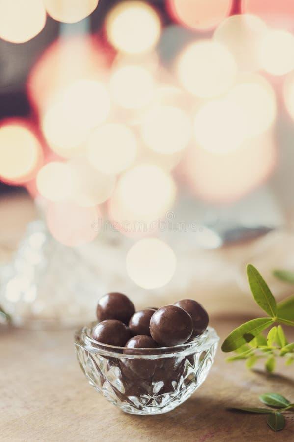 Chocoladedragee in een glaskom op peachy doek Het fonkelen lichten in de achtergrond en exemplaarruimte stock foto's