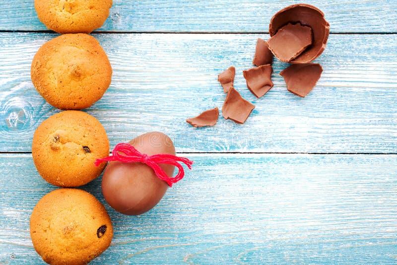 Chocoladeei en muffins op een blauwe houten achtergrond stock foto's