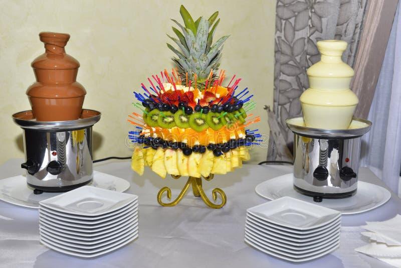 Chocoladefonteinen met vruchten op de lijst stock foto