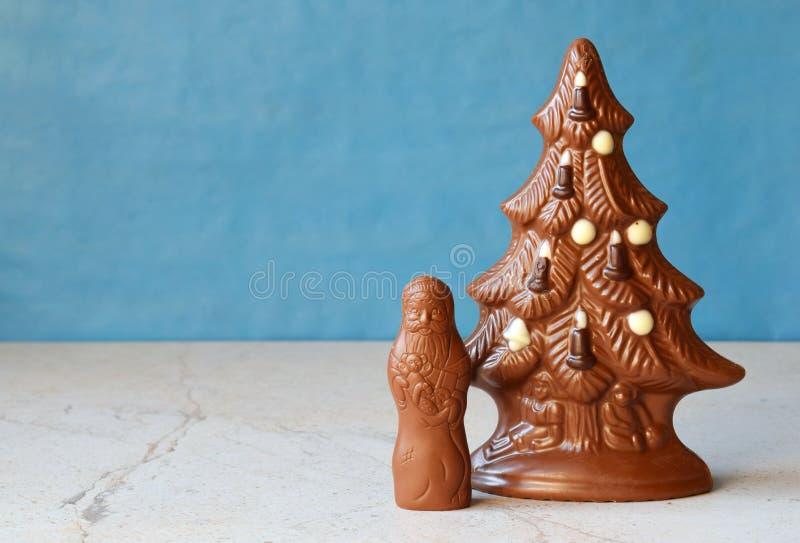 Chocoladekerstboom en Santa Claus op blauwe achtergrond Gelukkig nieuw jaar en Vrolijk Kerstmisconcept De ruimte van het exemplaa royalty-vrije stock afbeelding