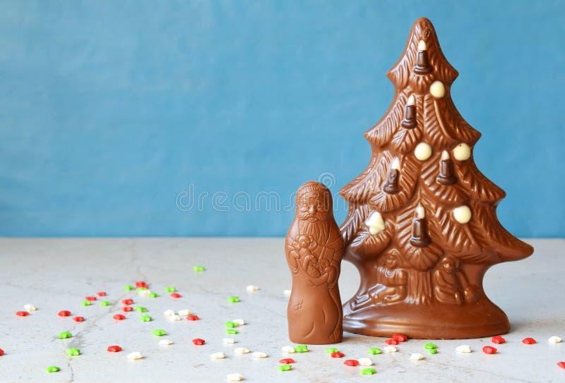 Chocoladekerstboom en Santa Claus op blauwe achtergrond Gelukkig nieuw jaar en Vrolijk Kerstmisconcept De ruimte van het exemplaa stock foto